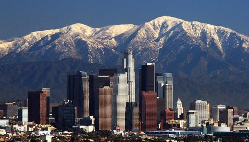 LA downtown with a backdrop of snowy mountains