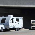 RVs parked under a bridge
